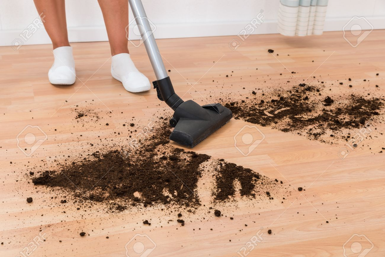 Close-up Of Person With Vacuum Cleaner Cleaning Dirt On Floor
